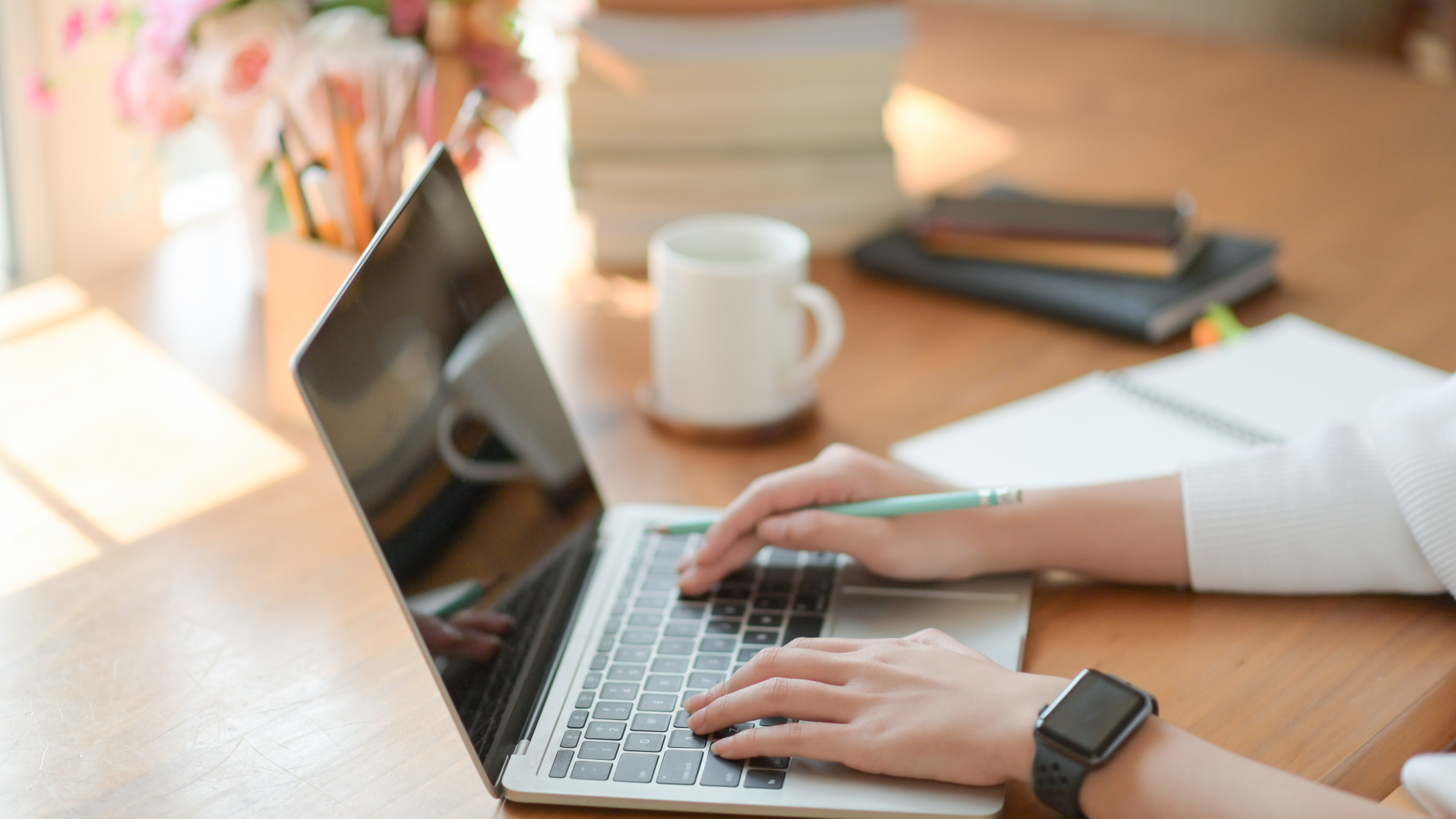 close-up-young-girl-hand-is-using-laptop-on-a-wood-R7FJDS2